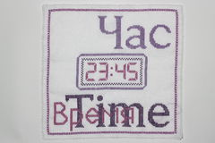 Time. Embroidery depicting clock in purple Royalty Free Stock Photography
