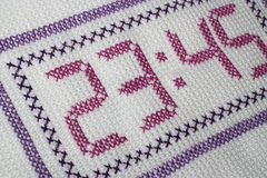 Time. Embroidery depicting clock in purple Stock Photography