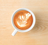 Time for espresso. Above capture of white coffee cup with tree shape latte art on wood table at cafe stock image