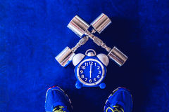Time for exercising alarm clock and dumbbell the Gym background. Share Time Healthy Concept Stock Photo