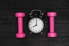 Time for exercising alarm clock and dumbbell Royalty Free Stock Image