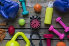 Time for exercising clock, dumbbell, fitness equipment. On wooden table background Royalty Free Stock Photo