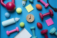 Time for exercising clock, dumbbell and fitness equipment. With yoga mat background Royalty Free Stock Images