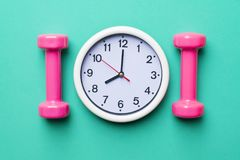 Time for exercising clock and dumbbell Royalty Free Stock Photo