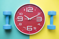 Time for exercising clock and dumbbell. With colorful background Stock Photography