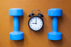 Time for exercising clock and dumbbell Royalty Free Stock Photography
