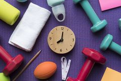 Time for exercising clock and fitness equipment. With yoga mat background Stock Image