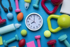 Time for exercising clock and fitness equipment. With yoga mat background Stock Photo