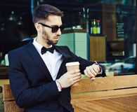 Time. Expectation. Coffee break. man, business man in a business suit and cup of coffee looking at the clock. City cafe Royalty Free Stock Image