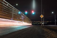 Time exposure photo with a street at night and automobile headlights and traffic light royalty free stock photography