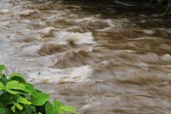 Time-exposure of Standing Waves in Readdies River. Time-exposure of standing waves in the muddy, rushing waters of the Readdies River after Hurricane Florence Stock Photography