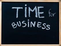 Time för affärsmeddelandet som är handskrivet med vit krita på träramsvart tavla Arkivbilder