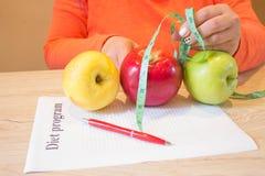 Time för bantar bantning Bantar begreppet, mat Kvinnlig och att mäta bandet och på tabellen Apple Royaltyfri Foto