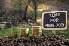 Time för det nya jobbet - finansiellt tillfällebegrepp Guld- mynt i svart tavla för jord på suddig naturlig bakgrund Royaltyfria Bilder