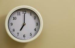 Time för 7:00 för väggklocka Arkivbild