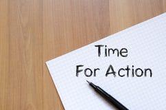 Time för handling skriver på anteckningsboken Arkivfoto