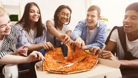 Time för mellanmål Lyckliga studenter som äter pizza och att prata royaltyfri foto