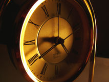 Time fading away. Old style mantel clock with roman numerals in ambient light royalty free stock photo