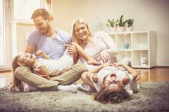 Time for family always exists. Young parents playing with daughters at home stock photos
