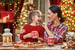 Time of family tea party. Merry Christmas and Happy Holidays. Time of family tea party. Mother and her child daughter are drinking warm tea with Christmas stock image