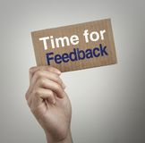 Time for feedback. Hand with brown card is showing Time for feedback with gray background Stock Photo