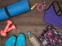Fitness time, everything is ready for a good workout. Time fitness-form, shoes, music player, water bottle, rug and dumbbells. Ahead of class training Stock Photos