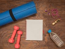 Fitness time, everything is ready for a good workout. Time fitness-form, shoes, music player, water bottle, rug and dumbbells. Ahead of class training Stock Image