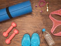 Fitness time, everything is ready for a good workout. Time fitness-form, shoes, music player, water bottle, rug and dumbbells. Ahead of class training Royalty Free Stock Photo