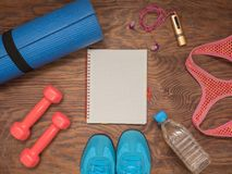 Fitness time, everything is ready for a good workout. Time fitness-form, shoes, music player, water bottle, rug and dumbbells. Ahead of class training Royalty Free Stock Photos