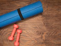 Fitness time, everything is ready for a good workout. Time fitness- rug and dumbbells. Ahead of class training Royalty Free Stock Photos