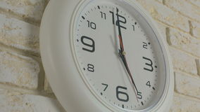 Time five hour. Timelapse. Round white clock hanging on brick wall. Time five hour. Timelapse. Round white clock hanging on a brick wall stock video