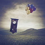 Time is fleeting. Old wooden pendulum flying in the sky with some colored balloons over a green meadow Stock Photos