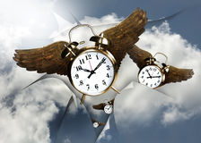 Time flies. Twin bell clocks with golden wings fly out of a tear in the sky Stock Photo