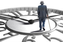 Time Flies. A senior walking on an enlarged clock depicting aging, retirement and time royalty free stock photos
