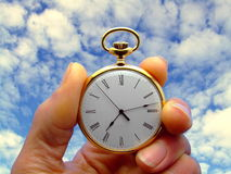 Time Flies. Close-up of a hand holding a pocket watch with a background of sky stock photography