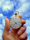 Time Flies. Close-up of a hand holding a pocket watch with a background of sky stock photo