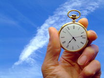 Time Flies. Close-up of a hand holding a pocket watch with a background of sky royalty free stock images