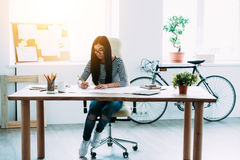 Time flies fast when you work with blueprints. Full length of young beautiful Asian woman drafting at blueprints while sitting at her working place Royalty Free Stock Image
