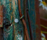 Time flies. Rusty nail in a piece of old wood. Rest of an old farm house stock images