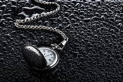 Time flows, watch with chain. Clock with chain photographed on background with water drops. This background gives elegance and power to the object, to the Royalty Free Stock Image