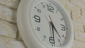 Time four hours thirty minutes. Timelapse. Round white clock hanging on brick wall. Time four hours thirty minutes. Timelapse. Round white clock hanging on a stock footage