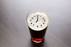 Time for fresh beer. Clock silhouette on foam in beer glass on black table, view from above Royalty Free Stock Photo