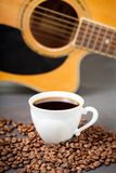 Time for fresh and tasty coffee. Sweet and tasty cup of coffee with blurred guitar on background. Musician morning routine concept royalty free stock photos