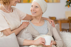 Time with friend. Smiling women suffering from cancer spending time with her friend Stock Image