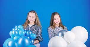 Time for fun. Adorable girls enjoy party time. Happy girls holding bunch of air balloons. Little girls having fun with stock photography