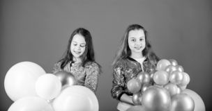 Time for fun. Adorable girls enjoy party time. Happy girls holding bunch of air balloons. Little girls having fun with royalty free stock image
