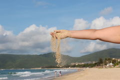 Time goes by. Hand that strews sand with sea and mountains on background Stock Images