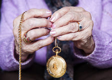 Time goes by. Old woman hands holding between her fingers a gold pocket watch Stock Photography