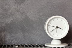Time goes by. Close up of a modern white clock against a grey background stock photos