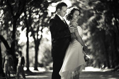 Time goes by - groom touches bride shoulders standing in the par Stock Image